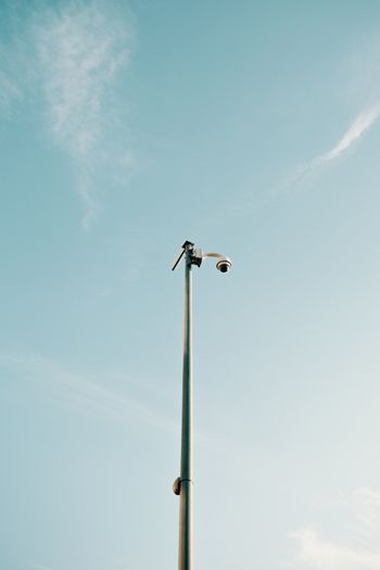 Minimalistic shot of a single vigilance camera in the top of a pole with the clean blue sky as the background