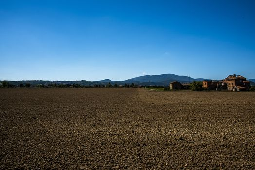 beautiful image of a brown plowed field with a blue sky in the background on the way to Citerna, Perugia, Umbria, Italy