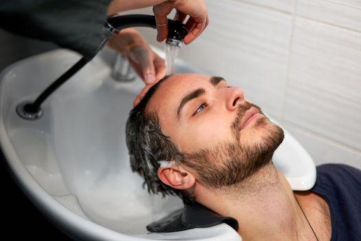 Woman applying shampoo massaging hair customer Man wash hair in beauty salon Hairdresser washing hair. Happy caucasian guy enjoy service in barbershop Preparing the client before hairdressing