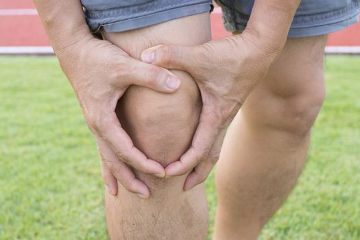 Tendon knee joint problems on Man leg from exercise In the stadium.