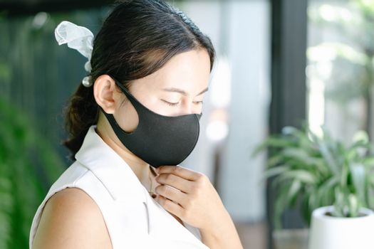 Closeup woman wearing face mask for protect air polution or virus covid 19 , health care and medical concept