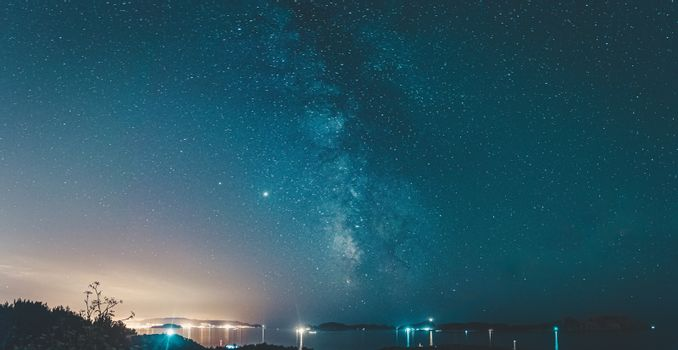 Panoramic view of the milky way over some islands
