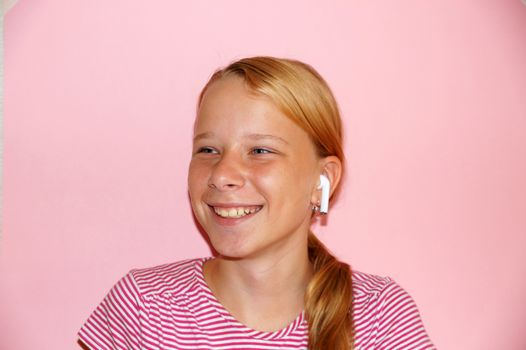 teenage girl listening to music on headphones and smiling, portrait on pink background.