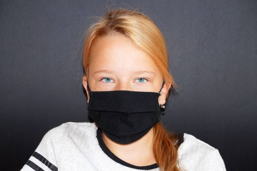 teenage girl in a black medical mask on a black background, portrait.