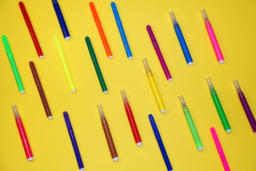 multicolored markers on a yellow background