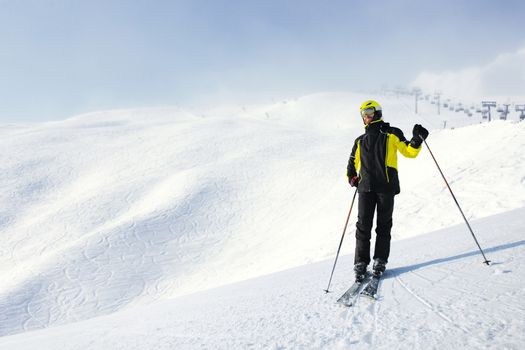 Skier standing on mountain slope