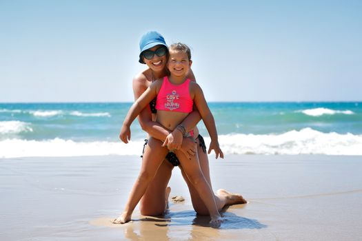 Cheerful Mother and Daughter Having Fun on the Beach. Happy Family With Pleasure Spending Time Together on the Beach Resort. Enjoying Holidays