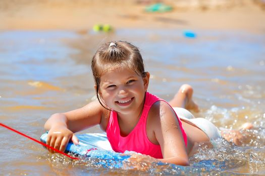 Portrait of a Cute Little Girl Having Fun on the Beach. Pretty Child Swimming on the Body Board in the Nice Warm Sea Water. Happy Active Summer Holidays.