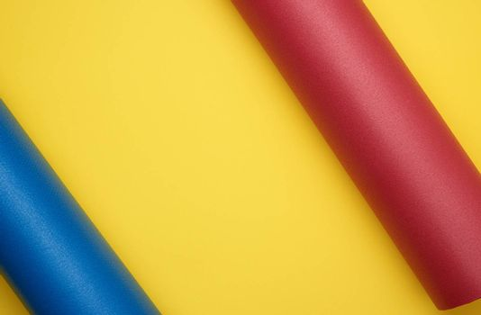 twisted red and blue neoprene mat for yoga and sports on a yellow background