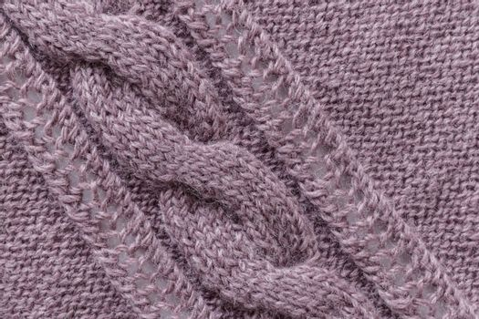Openwork pattern knitted with needles from pink wool yarn.