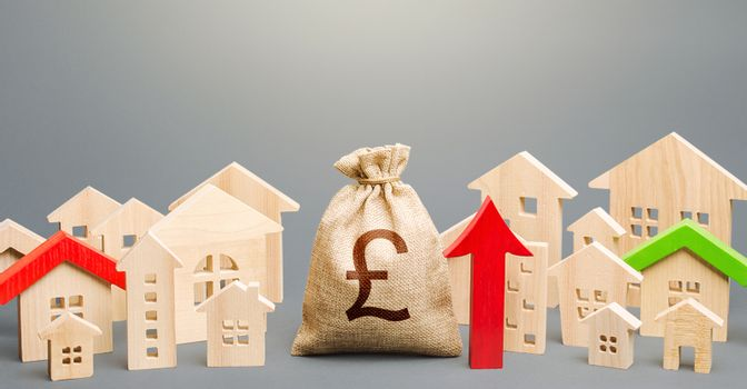 British pound sterling money bag and a city of house figures and red up arrow. Investments. Increase in revenues to municipal budget. Rent growth. Recovery and growth in property prices, high demand.