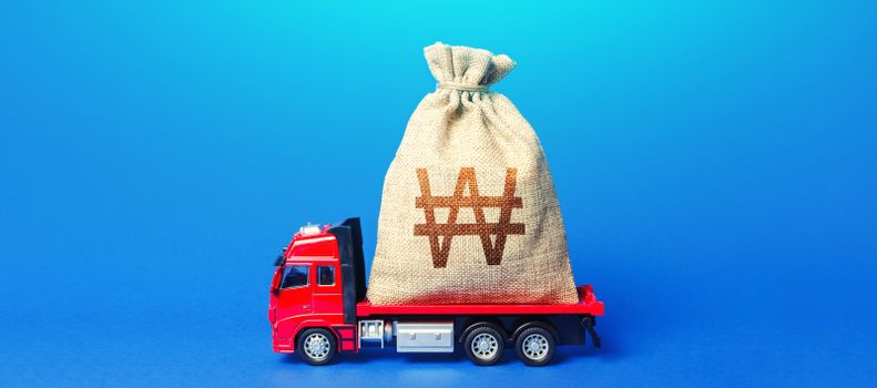 Truck is carrying a huge south korean won money bag. Anti-crisis measures of government. Great investment. Attracting large funds to economy for subsidies, support and cheap soft loans for businesses.