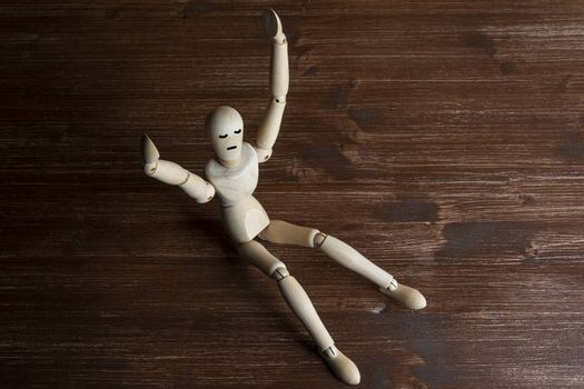 the joy on the face of a wooden mannequin with raised arms