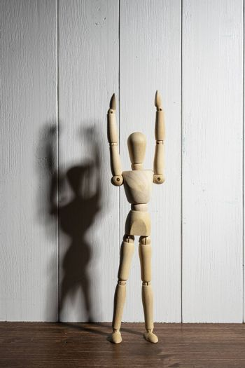 the  wooden mannequin with raised arms