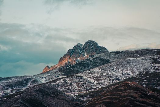 Panoramic view of a giant rock in the snowy mountain with the sunset reflecting on it