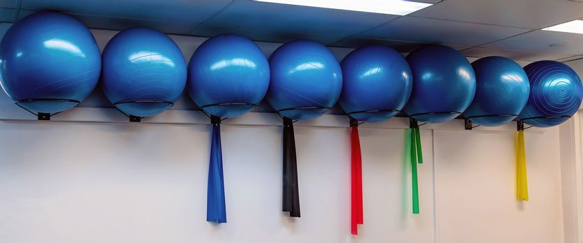 Large round blue pilates exercise balls in a row in a physiotherapist clinic