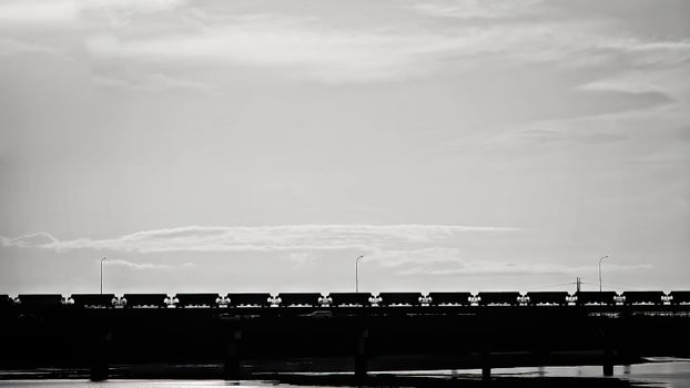 A rail freight train transporting cargo between destinations, as it crosses a river beside a bridge, rendered dramatically in black and white