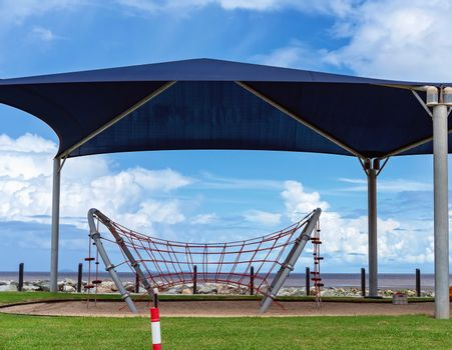 A beachfront shaded children's playground with climbing net