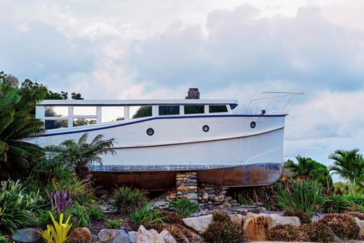 An old timber boat suspended on dry land in a landscaped garden