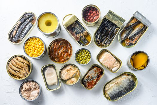 Assortment of canned preserves food in cans. On white rustic background conserve Saury, mackerel, sprats, sardines, pilchard, squid, tuna pinapple, corn, peas, mango , beans, top view.