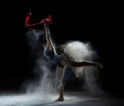 beautiful caucasian woman in a black bodysuit with a sports figure dancing with red ribbon on a black background, gymnastic exercises in flying white flour