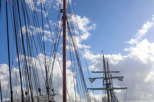 Sailing ship mast against the blue sky on some sailing boats with rigging details
