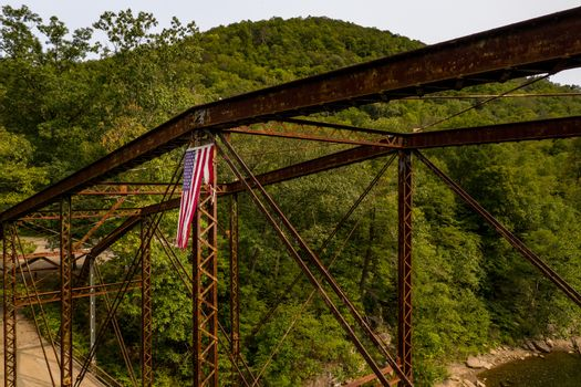 Drone view of torn USA flag on Jenkinsburg Bridge over Cheat River