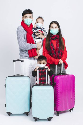 happy family wearing warm clothes and medical mask on white background. and Winter vacation concepts