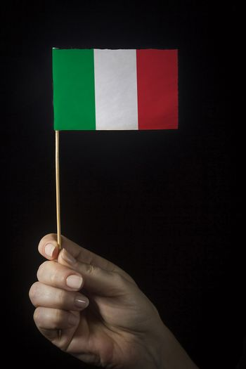 Hand with small flag of state of Italy