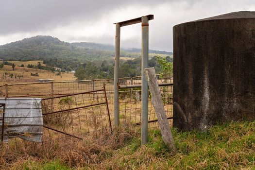 A concrete water tank and old broken down fencing on a run down dairy property