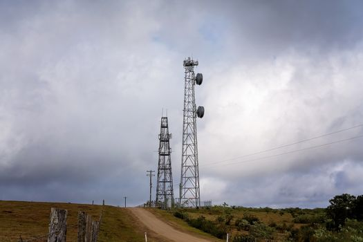 Modern technology communication towers beside a dirt road in a rural setting