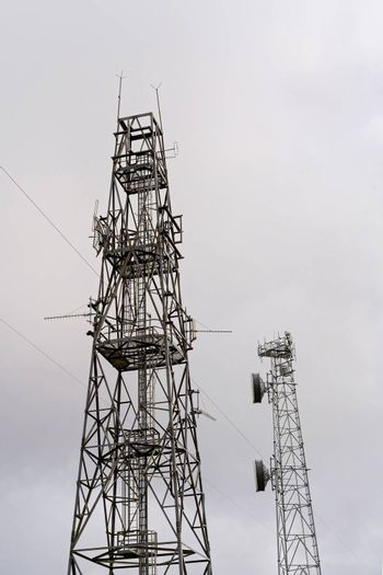 Modern technology communication towers against a bright sky