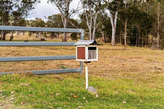 A retro style mail box in front of a fence on a rural property