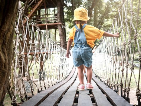 Rear view of the young girl was walking on suspension wooden bridge with nets or rope handrails in the park playground.