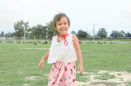 Happy child girl having fun in sheep farm.