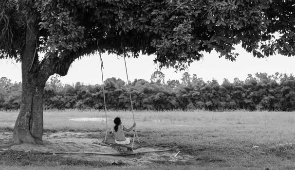 Rear of child girl playing swing outdoor in the park. Black and white style tone.