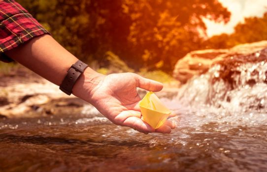 Close up of Woman's hand putting paper boat on the water and pushing it away with reflection sunshine in the water background, as in childhood.