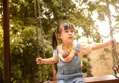 Happy child girl playing swing outdoor in the park on summer time. Concept of Childhood happiness.