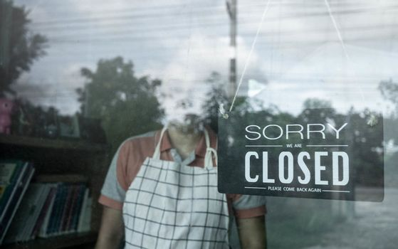 The woman store owner hanging closed sign in front door of her shop. Effect of corona virus or covid-19 outbreak 2020.