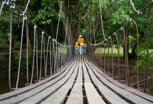 Rear view of family walking on suspension wooden bridge with nets or rope handrails in the park.