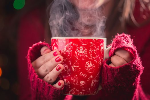 Detail of woman hands holding warm a cup of tea with steam. Blur Christmas background. Christmas or winter concept.