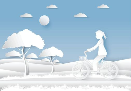 Girl riding a bicycle in the field on blue sky paper art, paper cut style background