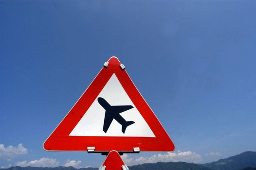 airplane symbol on red triangle traffic sign, blue sky background