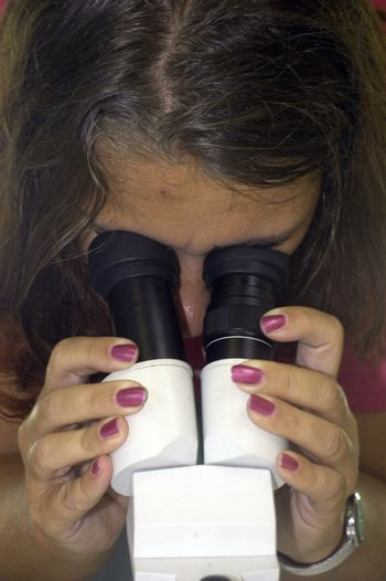 female scientist in a research lab watching through a microscope