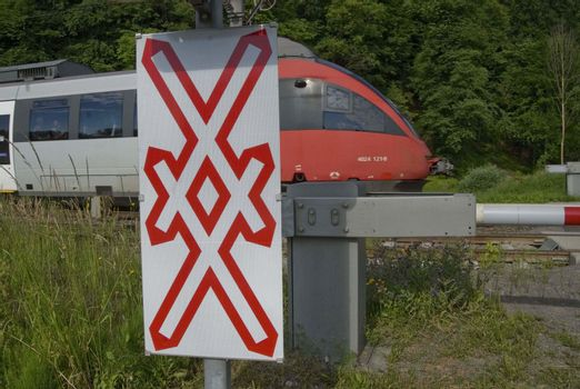 a train is crossing a gated level crossing with cross buck