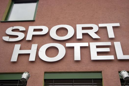 a white Sport Hotel sign on a red painted building