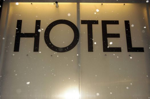 a black Hotel sign with snow falling down in front of it