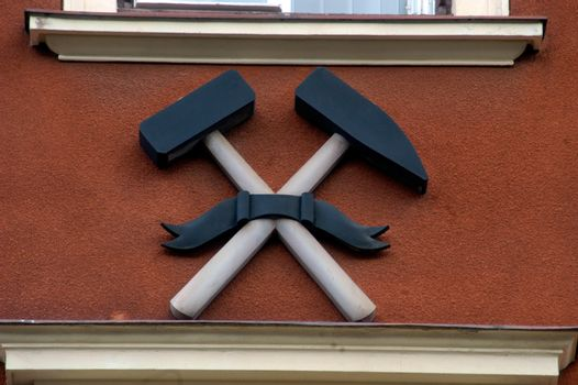a crossed hammer and pickaxe, mining symbol on a building