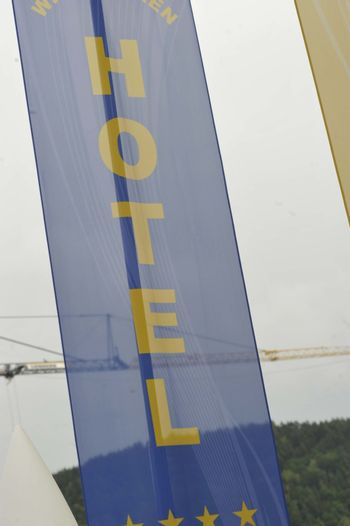 a blue Hotel banner with yellow font on it standing outdoors