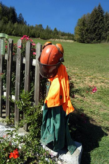chainsaw safety clothing hanging on a fence in the garden